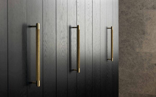 Black oak panelled doors and stone tiles | bathroom | auckland villa